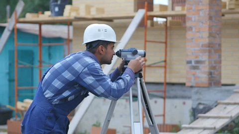 Surveyor performs measuring operations on the level and the theodolite