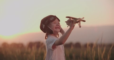 close-up shot of happy boy with toy airplane in wheat field running. dream, childhood, memories concept.Slow motion, sunset time.