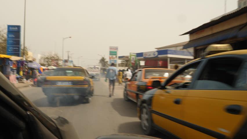 Senegal, Africa, June 2018. Old taxi creating cloud of exhaust fumes/air pollution. Dakar.