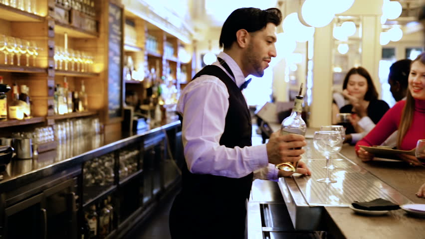 Smiling bartender pouring beverages and talking to cheerful visitors in bar