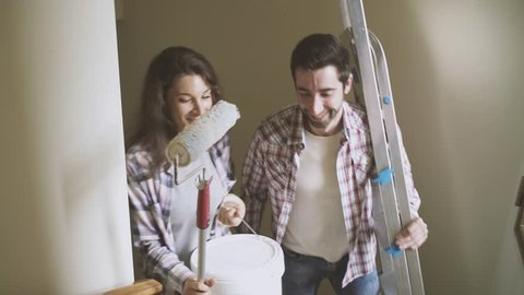 Young couple renovating their new house, they are carrying wall painting tools and going upstairs to their apartment: lifestyle and home renovation concept