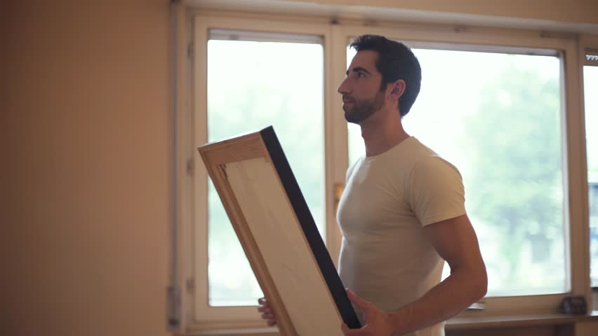 Young couple moving in their new house and decorating walls, the man is hanging a painting on the wall and his girlfriend is smiling   Shutterstock HD Video #1012476356