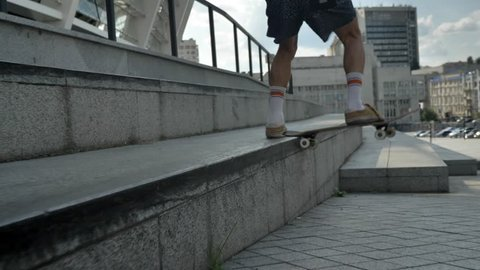 Skateboarder doing skateboard trick on stairs and sitting down on stair in modern city