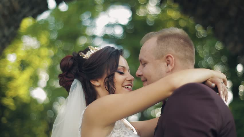 Lovely wedding couple standing together in the park | Shutterstock HD Video #1012519076