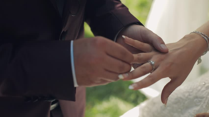 The geoom puts on the wedding ring to the bride | Shutterstock HD Video #1012519106
