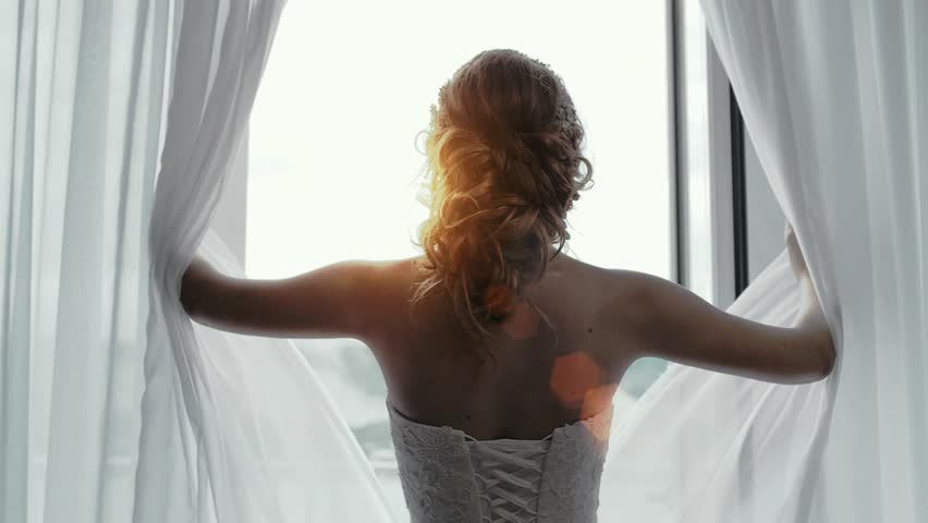 A girl in an easy white dress opens curtains and looks at the sun #1012525346