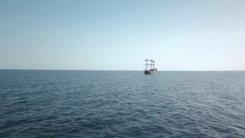 A pirate sailboat in the blue waters of the ocean. far view.
