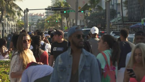 Miami beach cityscape, street view. Crowd of students and tourists walking on the Ocean drive in South Beach at spring break time - April 2018: Miami beach, Florida, US