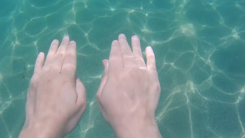 Hands swimming under the water. Subjective point of view. Sea. Woman hands.