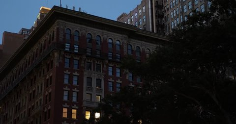 A nighttime establishing shot (NX) of a typical red brick apartment or office building in midtown Manhattan, New York. Day/Night matching available.