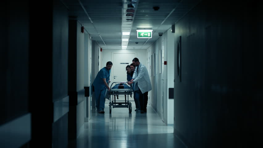 Emergency Department: Doctors, Nurses and Paramedics Run and Push Gurney / Stretcher with Seriously Injured Patient towards the Operating Room. Shot on RED EPIC-W 8K Helium Cinema Camera.