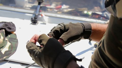 men's gloved hands untangle fishing line. unravel the tangle of fishing line on the background of the boat