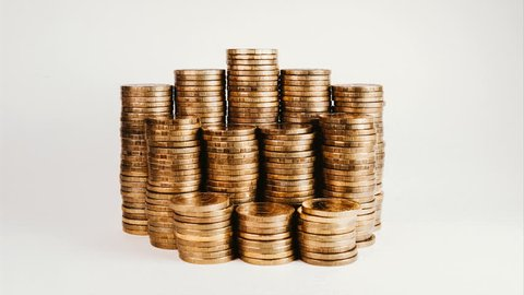 Stop motion reduction of a pile of gold coins, reduced investment and reduced profits on a white isolated background.