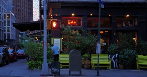 A nighttime summer establishing shot of a typical corner Manhattan bar or restaurant entrance.