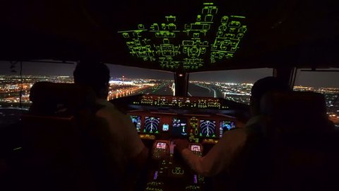 Two pilot were operating the airplane in landing phase. Airplane was touching down on the runway in airport at night, able to see beautiful view of cityscape and lights of runway from inside cockpit.