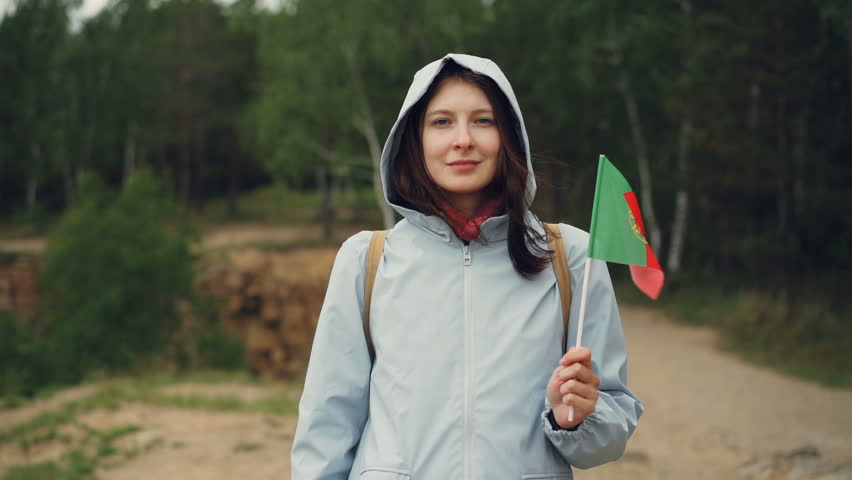 Slow motion portrait of attractive Portuguese girl holding flag of Portugal, smiling and looking at camera. Citizens, national pride, springtime concept.