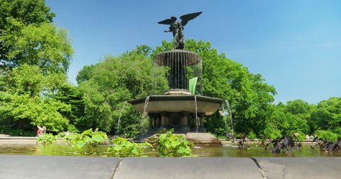 A slow low angle dolly establishing shot of Bethesda Fountain in New York City's iconic Central Park on a summer day as tourist mill around in the distance.