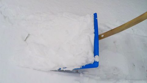 Removing snow with snow shovel from the sidewalk after snowstorm.