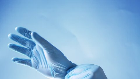 Doctor put on blue latex gloves, closeup