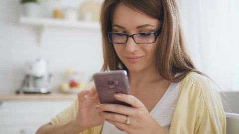 Beautiful woman with brown hair, in glasses and yellow cardigan texting to her friends on brand-new smartphone and smiling in the kitchen. Indoors. Portrait.