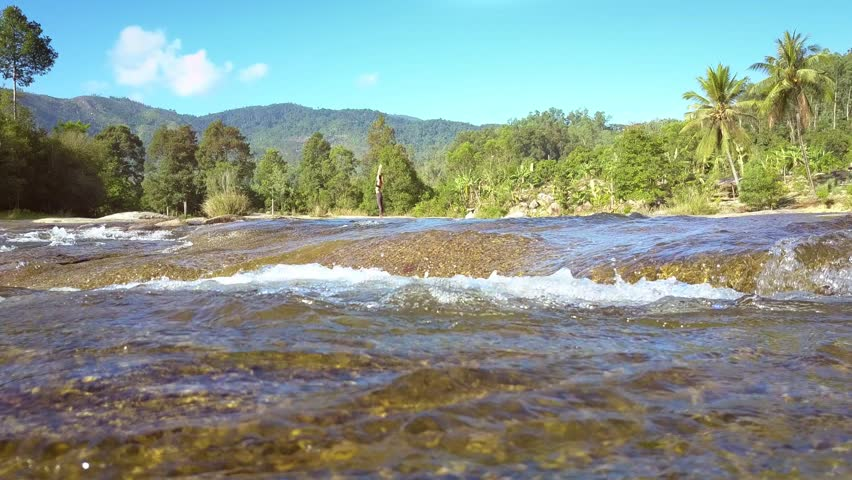 Closeup transparent river flows stream fast against pictorial green landscape and distant mountains