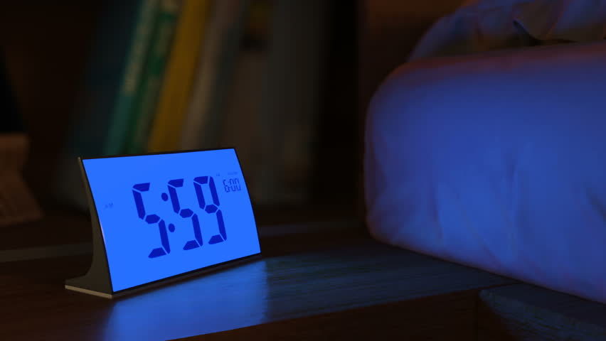 Digital alarm clock waking up at 6 AM. Close-up view. The numbers on the clock screen changes from 5:59 no 6:00 AM. Then alarm logo appears on the screen. 3D rendering animation.