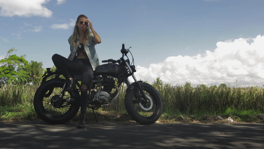 Sexy girl in casual jeans sit on classic style cafe racer motorcycle. Modern woman correct her hair. Bike custom made in vintage garage. Brutal fun urban lifestyle. Outdoor portrait. | Shutterstock HD Video #1012729376