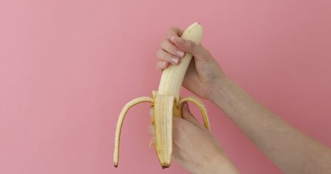 Female hands hold phallic fruit play and imitates jerk. Close up of peeled banana representing man penis while masturbating on pink background