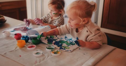 Happy little sisters having fun painting watercolor drawings in family home kitchen