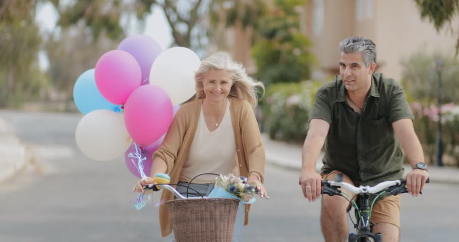 Happy retired married couple enjoying bike ride together on sunny day in spring