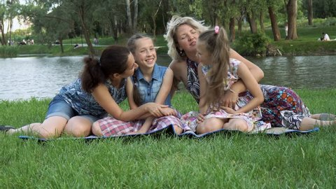 Same-sex family: two mothers with two daughters play, laugh and have fun sitting in the Park on the lawn at sunset near the river. 4K, 29.97 fps.