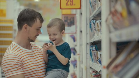 Footage father and son buy lollipop in a store