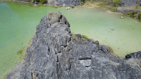 A cinematic aerial drone shot of a man looking over a tropical green quarry lake on an island off the coast of Powell River, British Columbia. He looks over a cliff.