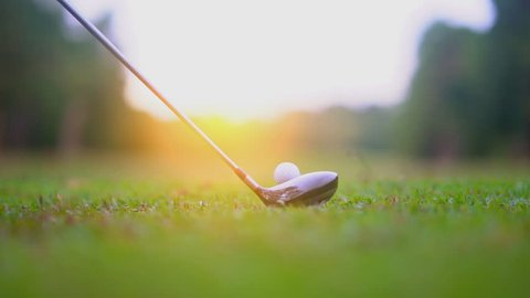Slow motion golf sport concept, golfer hitting golf ball to hole for winner in golf course is beautiful fairway on sunset. Close up shot tee off on green grass for player playing in summer for relax