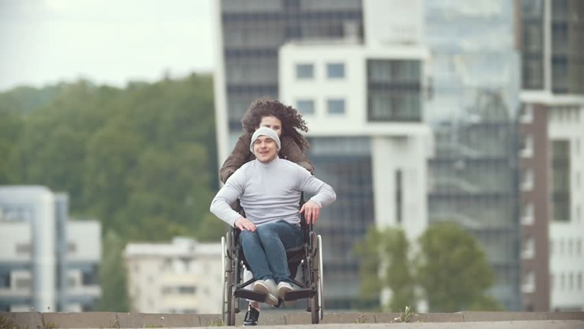 Happy disabled man in a wheelchair with happy young woman running at the city street | Shutterstock HD Video #1012801886