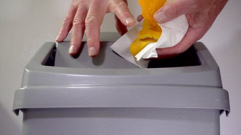 Slow motion close shot of a man's hands putting orange peel from a piece of kitchen towel into a plastic swing bin / trash can.