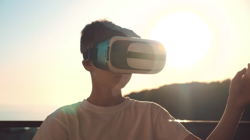 Happy boy at sunset, wearing virtual reality glasses, playing video games Cheerful smiling, looking in VR glasses and hand gesture.