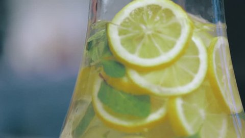 Stirring Icy Lemon Water with Thyme as Refreshment for House Party