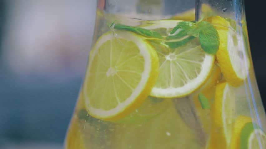 Stirring Icy Lemon Water with Thyme as Refreshment for House Party | Shutterstock HD Video #1012851656