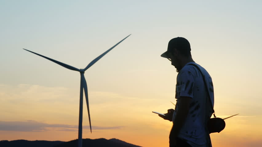 the silhouette of young man with beard and sunglasses using smartphone mobile while standing against the windmill farm with summer setting sun on background modern eco system nano technology app