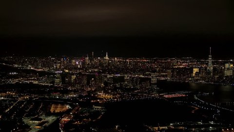 AERIAL HELI SHOT: Flying above New Jersey port in industrial zone at night, overlooking iconic NYC Downtown skyline with brightly lit skyscrapers WITH Brooklyn and Queens cityscape in the background