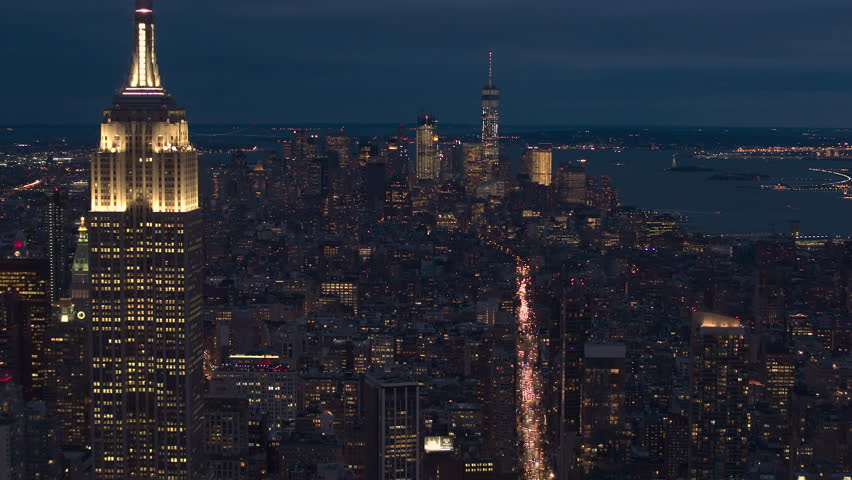 AERIAL HELI SHOT, CLOSE UP: Flying above New York City skyscrapers and blocks of flats lit up with glowing lights by night. Cars driving from Downtown Manhattan on busy sixth avenue full of traffic | Shutterstock HD Video #1012862006