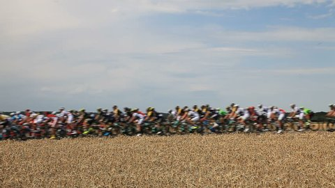 Vendeuvre-sur-Barse, France - 6 July, 2017: Slightly out of focus and blurred HD footage of the peloton passing through a region of wheat fields during the stage 6 of Tour de France 2017.
