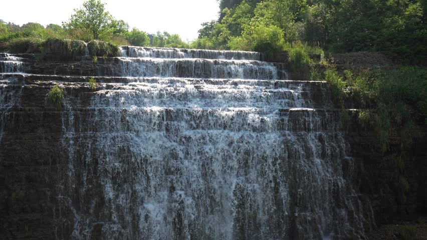 View of the beautiful Thunder Bay Waterfall with water pouring over the rocky stepped cliff located along a road in Galena Illinois.