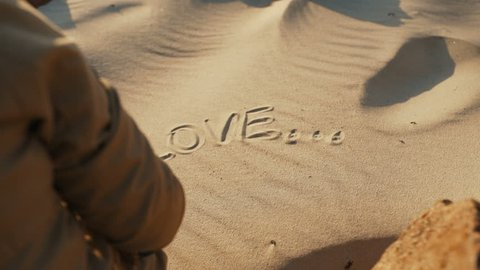 """A girl in the sand draws the word """"love"""". Girl draws a symbol of the heart and love on the sandy beach, rear view, close-up. The concept of love. 4k"""