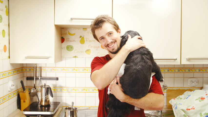 Man carry dog on shoulder turn around with smile 4K. Static medium shot of man and small dog in focus while cooking in kitchen and dog looking over shoulder around. | Shutterstock HD Video #1012878026