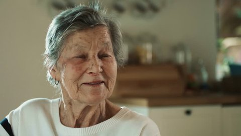 An elderly woman at home talking to somebody and laughing.