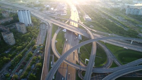 Aerial view. Flyght over a huge interchange of the Moscow ring road in the early morning at sunrise from high altitude. Cars are moving on a multi-level road junction. Urbanistic scenery.