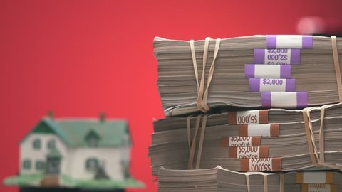 Focus pull between a pile of money and a house model.