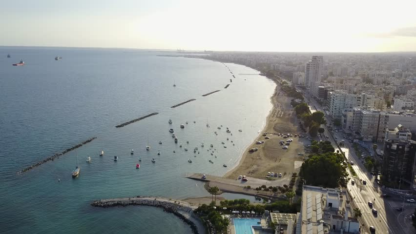 Aerial drone shot over the coast of Limassol city zooming in on beach and boats